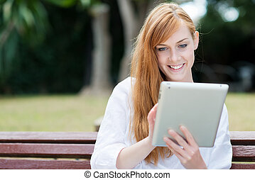 Young woman sitting in a park with her tablet-pc