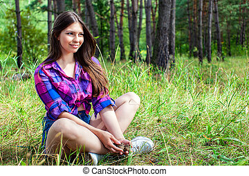 Young woman sitting in a pine tree forest
