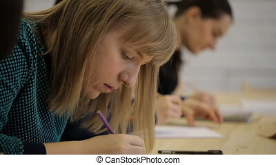 Young woman sitting in a row with others on classroom for drawing.