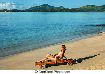 Young woman sitting in a sun chair on the beach