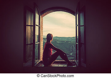 Young woman sitting in an open old window looking on the...