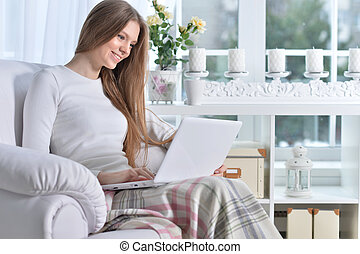 Young woman sitting in armchair using laptop