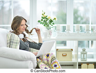 woman sitting in armchair using laptop