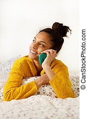 Young woman sitting in bed and talking on mobile phone