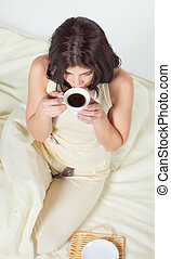 Young woman sitting in bed drinking coffee