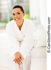 young woman sitting in bedroom