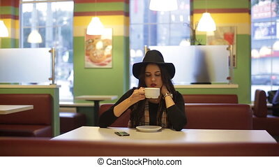 Young woman sitting in cafe and dreams