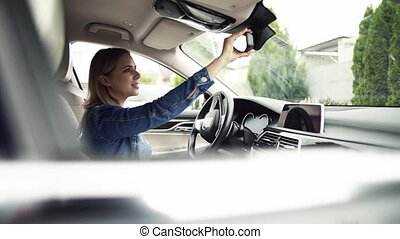 Young woman sitting in car, adjusting rear view mirror. Slow...