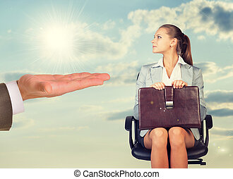 Young woman sitting in chair and looking at mans hand