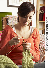 Young Woman Sitting In Chair Knitting