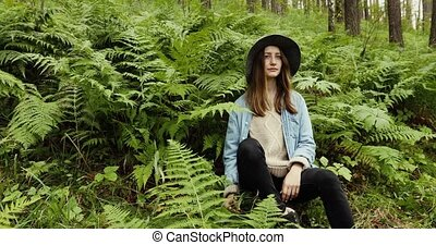 Young woman sitting in forest with high trees