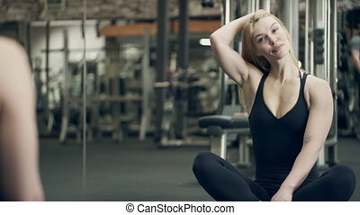 Young woman sitting in front of mirror on floor gym....