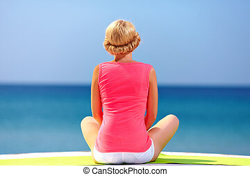 young woman sitting in front of the seaside