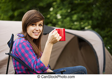 Young woman sitting in front of the tent