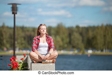 Young woman sitting in lotus position on the forest lake