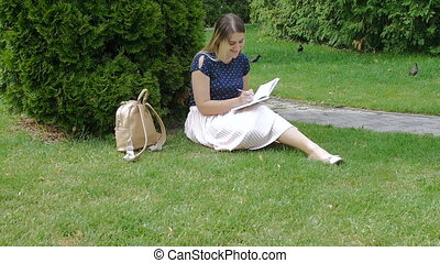 Young woman sitting in park on grass and writing a diary