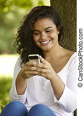 Young Woman Sitting In Park Sending Text Message