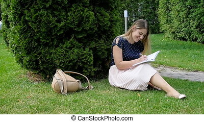 Young woman sitting in park with a diary - Young woman...