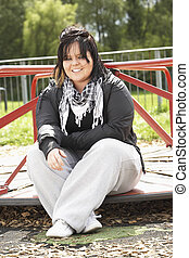 Young Woman Sitting In Playground