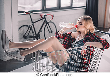 Young woman sitting in shopping cart and drinking water