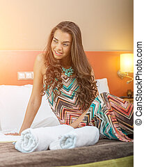 Young woman sitting in the bed of a hotel room