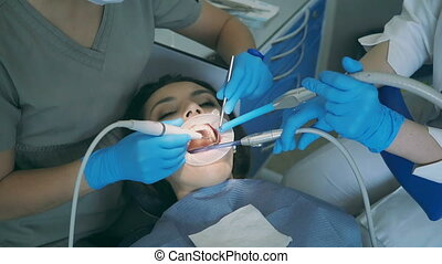 Young woman sitting in the dental chair with opening wide...
