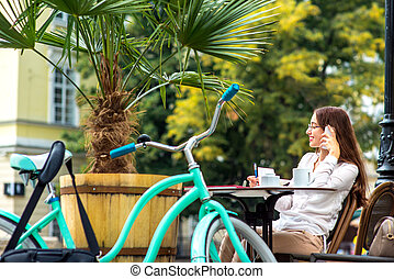 Young woman sitting in the open air cafe with cup of coffee and bicycle and speaking phone in the morning in the city centre