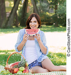 Young woman sitting in the park and eating a watermelon.