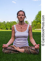 Young woman sitting in yoga pose meditation outdoors