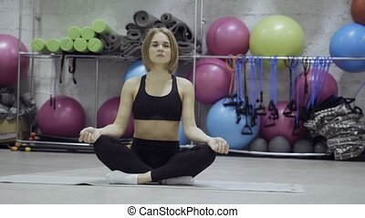 Young woman sitting in yoga pose on the mat over different ...