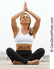 Young woman sitting in yoga pose outdoors