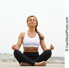Young woman sitting in yoga pose outside