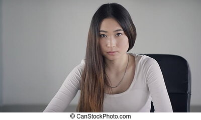 Young woman sitting inside office and looking at camera....