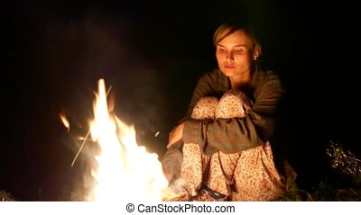 young woman sitting near a fire on the beach and sad