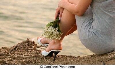 young woman sitting near a lake