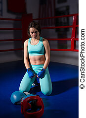 Young woman sitting near lying boxing gloves and helmet in ring