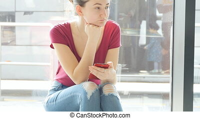 Young woman sitting near window at airport waiting lounge and looking around and then using a smartphone. Expectations of flight at airport. Close up