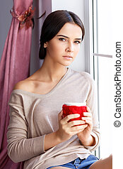 Young woman sitting near window - Revel in aroma. Pleasant...