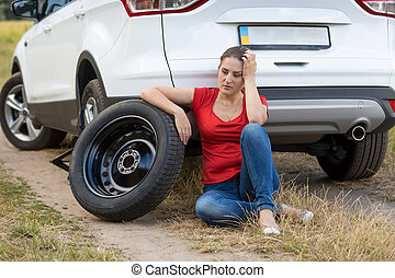 Young woman sitting next to the car with flat tire