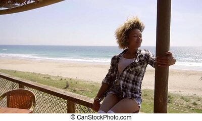 Young woman sitting on a beachfront balcony