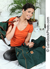 Young woman sitting on a bed with luggage