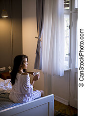Young woman sitting on a bed with mug in bedroom