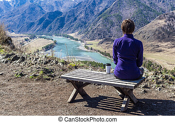 Young woman sitting on a bench and looking at a river with a cup of tea