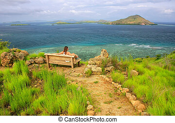 Young woman sitting on a bench at the viewpoint on Kanawa Island in Flores Sea, Nusa Tenggara, Indonesia