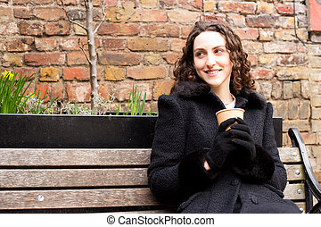 young woman sitting on a bench enjoying a coffee