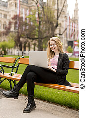Young woman sitting on a bench in park with a laptop
