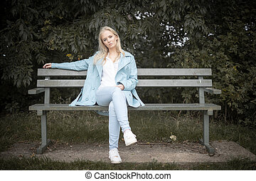 Young Woman Sitting On A Bench In The Park