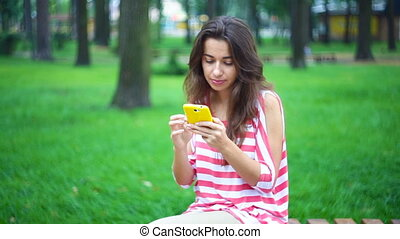 young woman sitting on a bench in the summer park with a smartphone
