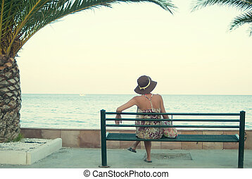 young woman sitting on a bench near the sea