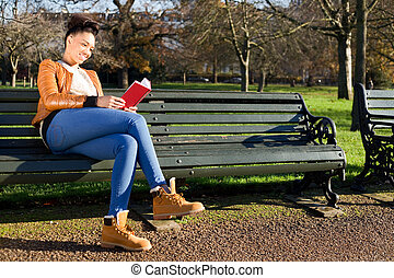young woman sitting on a bench reading a book